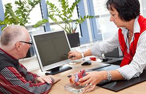 Aufklärungsgespräch, Ärztin zeigt auf Daten am PC-Bildschirm und erklärt am Herzmodell.